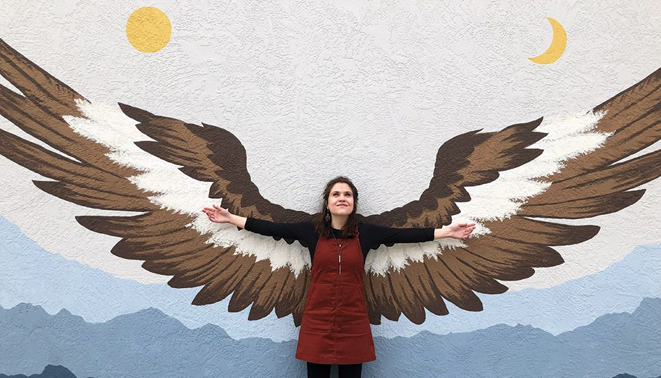 A woman stands in front of a mural depicting painted wings
