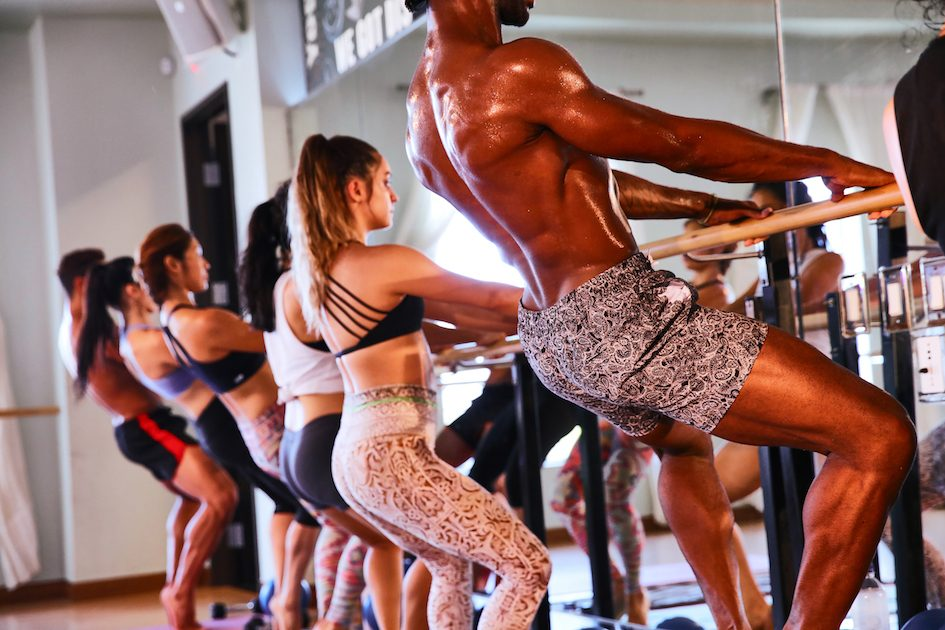 People wearing exercise gear work out at a ballet barre, in a Barre class at TruFusion Washington