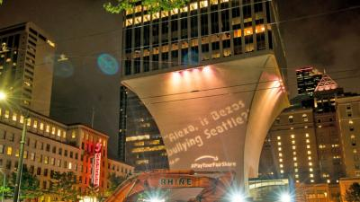 Projection criticizing Amazon in Seattle on Fourth and Union