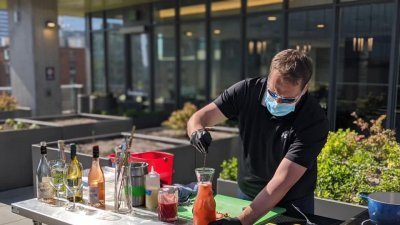 Bar tender serves happy hour to Murano Residents during social distancing